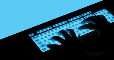 Hands typing on blue, light up keyboard